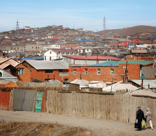 Locals walk along a dirt road running alongside a township of make-shift houses in the Mongolian capital city of Ulan Bator