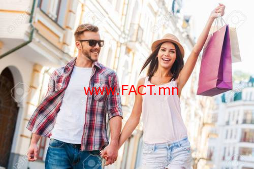 We love shopping together! Beautiful young loving couple walking by the street while beautiful woman carrying shopping bags and smiling