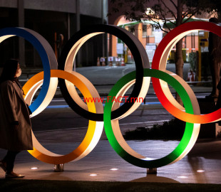 A woman wearing a protective face mask, following the outbreak of the coronavirus, walks past The Olympic rings in front of the Japan Olympics Museum in Tokyo